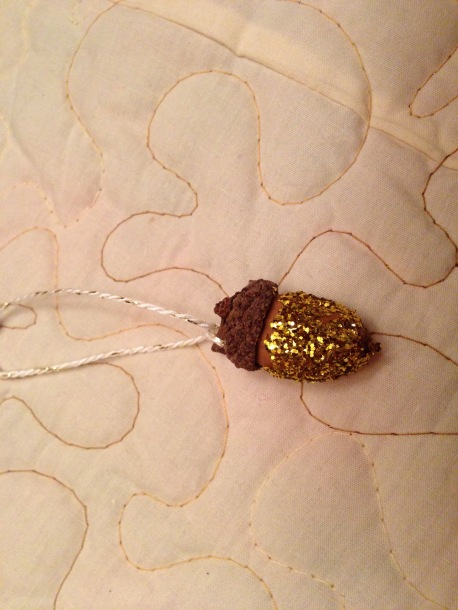 Glitter acorn ornament in gold.